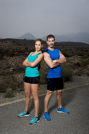 attitude girl: young sport couple posing shoulder to shoulder looking cool and defiant attitude girl wearing cyan tank top and man blue singlet both with folded arms in fitness club advertising style