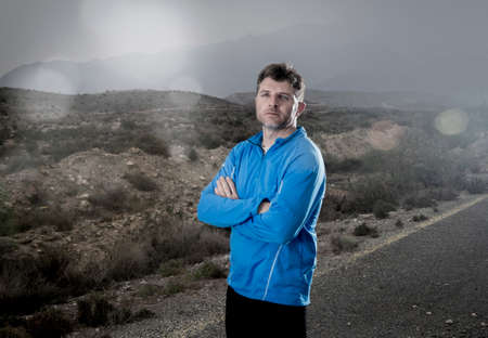 defiant: young attractive sport man with folded arms posing cool and defiant attitude in dramatic advertising light style outdoors on mountain landscape after running workout