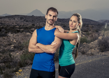 attitude girl: young sport couple posing shoulder to shoulder looking cool and defiant attitude girl wearing cyan tank top and man blue singlet  with folded arms in fitness club advertising style