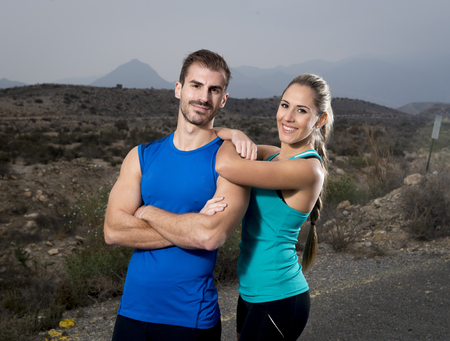 singlet: young sport couple posing shoulder to shoulder looking cool and smiling happy  girl wearing cyan tank top and man blue singlet both with folded arms in fitness club advertising style