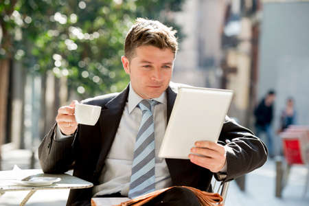 eye pad: young attractive businessman sitting outdoors in coffee break holding cup and digital tablet pad checking onl?ne news in internet technology communication and business concept Stock Photo