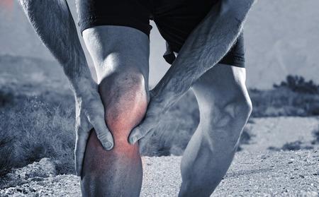 Młody człowiek z silnymi sportu lekkoatletycznych nogi trzymając kolano z rękami w bólu po doznaniu kontuzji mięśni podczas treningu biegowego treningu w pustynny szlak polnej drodze w czerni i bieli