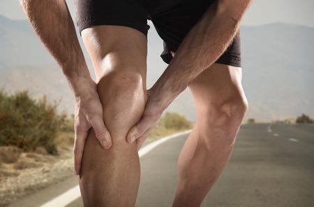 muscular: deporte hombre joven con fuertes piernas atl�ticas que sostienen la rodilla con las manos en el dolor despu�s de sufrir una lesi�n muscular durante una sesi�n de ejercicios de entrenamiento que se ejecuta en la carretera de asfalto en la herida musculares o de ligamentos