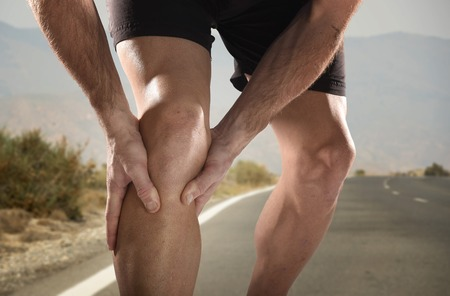 hand pain: young sport man with strong athletic legs holding knee with his hands in pain after suffering muscle injury during a running workout training in asphalt road in muscular or ligament wound