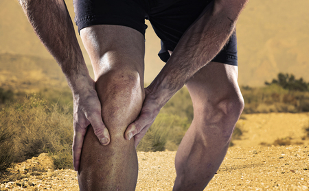 contracture: young sport man with strong athletic legs holding knee with his hands in pain after suffering muscle injury during a running workout training in trail desert dirt road