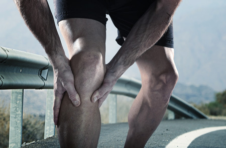 young sport man with strong athletic legs holding knee with his hands in pain after suffering muscle injury during a running workout training in asphalt road in muscular or ligament wound