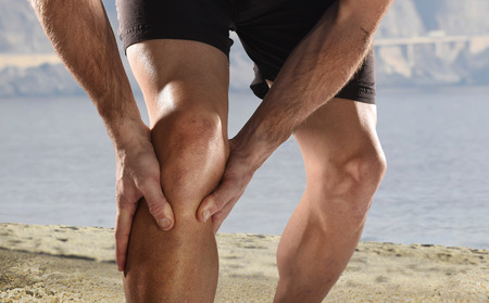 muscular: deporte hombre joven con fuertes piernas atl�ticas que sostienen la rodilla con las manos en el dolor despu�s de sufrir una lesi�n muscular durante un entrenamiento Entrenamiento de la playa que se ejecuta en la herida musculares o de ligamentos