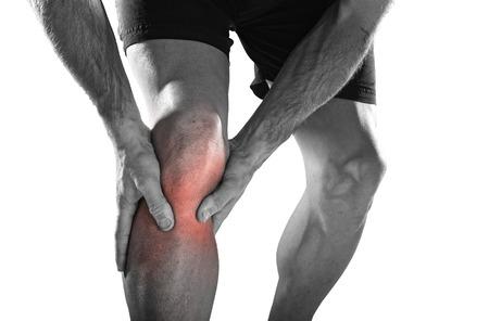 piernas hombre: deporte hombre joven con fuertes piernas atléticas que sostienen la rodilla con las manos en el dolor después de sufrir una lesión de ligamentos durante una sesión de ejercicios de entrenamiento ejecutando aislados sobre fondo blanco en blanco y negro