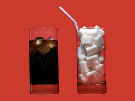 dos vasos de vidrio de una bebida refrescante de cola y otro lleno de terrones de azúcar y paja que representan a la gran cantidad de contenido de calorías en la soda en concepto de nutrición poco saludable aislado en fondo rojo Foto de archivo