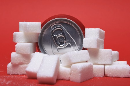 cola refreshing drink can and lot of white sugar cubes representing the big amount of calories content in the soda in unhealthy nutrition concept isolated on red background Stock Photo