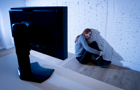 cyber bullying: young teenager woman abused suffering internet cyberbullying scared sad and depressed in fear face expression sitting on the floor in front of computer monitor in cyber bullying social problem concept
