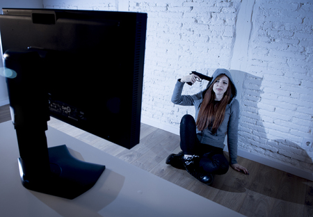 tempo: young teenager woman abused suffering internet cyberbullying scared and desperate pointing gun to her tempo in suicide gesture in front of computer monitor in cyber bullying concept Stock Photo