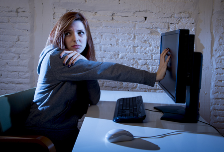 cyber bullying: young teenager woman abused suffering internet cyberbullying scared sad and depressed in fear face expression sitting in front of computer monitor in cyber bullying social problem concept