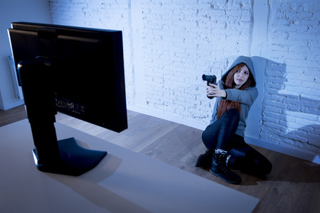 pointing gun: young teenager woman abused suffering internet cyberbullying scared and desperate defending herself pointing gun to computer monitor in cyber bullying concept Stock Photo