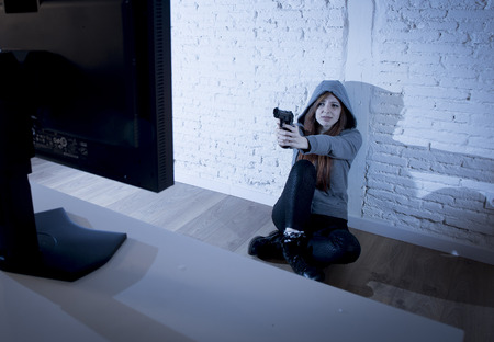 cyber bullying: young teenager woman abused suffering internet cyberbullying scared and desperate defending herself pointing gun to computer monitor in cyber bullying concept Stock Photo