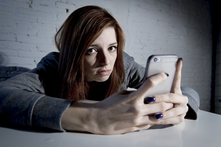 vulnerable: young sad vulnerable girl using mobile phone scared and desperate suffering online abuse cyberbullying being stalked and harassed in teenager cyber bullying concept Stock Photo