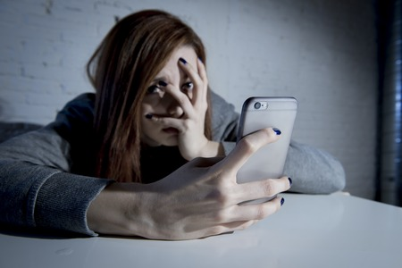 cyber woman: young sad vulnerable girl using mobile phone scared and desperate suffering online abuse cyberbullying being stalked and harassed in teenager cyber bullying concept Stock Photo