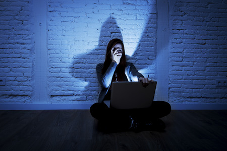 humiliated: sad and scared female teenager with computer laptop suffering cyberbullying and harassment being online abused by stalker or gossip feeling desperate and humiliated in cyber bullying concept Stock Photo