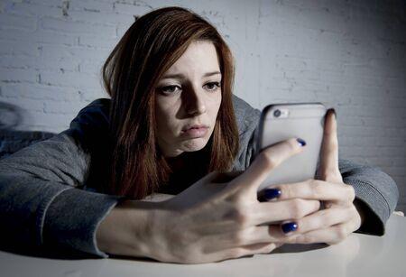 asustado: ni�a triste vulnerables usando el tel�fono m�vil asustado y desesperado que sufren acoso cibern�tico abuso en l�nea siendo acosados ??y hostigados en adolescente concepto de acoso cibern�tico