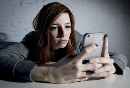scared girl: young sad vulnerable girl using mobile phone scared and desperate suffering online abuse cyberbullying being stalked and harassed in teenager cyber bullying concept Stock Photo