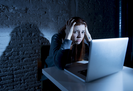 sad and scared female teenager with computer laptop suffering cyberbullying and harassment being online abused by stalker or gossip feeling desperate and humiliated in cyber bullying concept Stock Photo