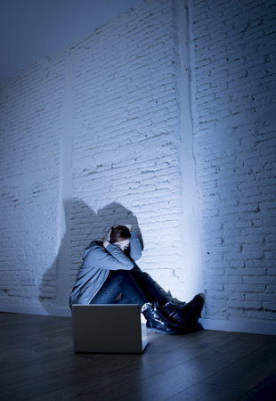 sad and scared female teenager with computer laptop suffering cyberbullying and harassment being online abused by stalker or gossip feeling desperate and humiliated in cyber bullying concept Banco de Imagens