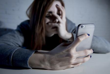 jonge droevige kwetsbaar meisje met behulp van mobiele telefoon bang en wanhopig lijden online misbruik cyberpesten wordt gestalkt en lastig gevallen in tiener cyberpesten begrip