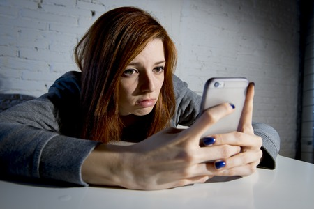young sad vulnerable girl using mobile phone scared and desperate suffering online abuse cyberbullying being stalked and harassed in teenager cyber bullying concept Reklamní fotografie