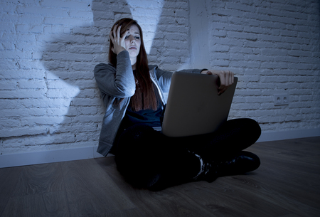 harassing: sad and scared female teenager with computer laptop suffering cyberbullying and harassment being online abused by stalker or gossip feeling desperate and humiliated in cyber bullying concept Stock Photo