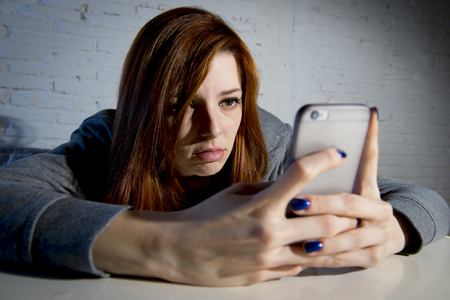 threatened: young sad vulnerable girl using mobile phone scared and desperate suffering online abuse cyberbullying being stalked and harassed in teenager cyber bullying concept Stock Photo