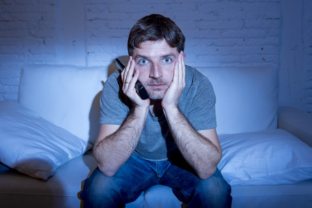 eyes wide open: young attractive man at home lying on couch at living room watching tv holding remote control looking mesmerized with blue eyes wide open in television addict concept Stock Photo