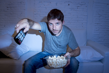 changing channel: young attractive man at home lying on couch at living room watching tv holding remote control and changing channel or volume