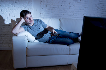 changing channel: young attractive man at home lying on couch at living room watching tv holding remote control and changing channel or volume looking interested and relaxed