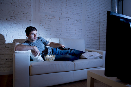 confortable: young attractive man at home lying on couch at living room watching tv holding remote control and changing channel or volume looking interested and excited with comedy movie or sitcom