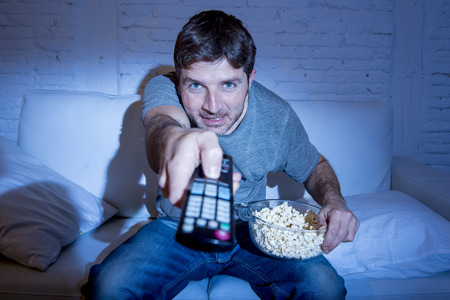 changing channel: young attractive man at home lying on couch at living room watching tv eating popcorn bowl using remote control and changing channel or volume looking interested and excited in television fan concept