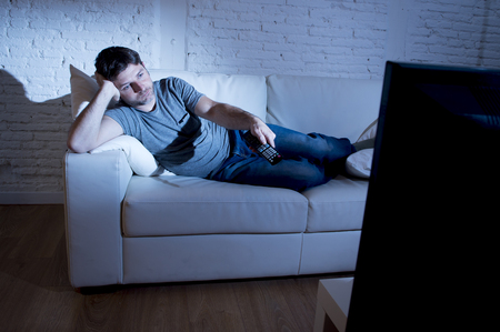 young attractive man at home lying on couch at living room watching tv holding remote control and changing channel or volume looking bored Foto de archivo