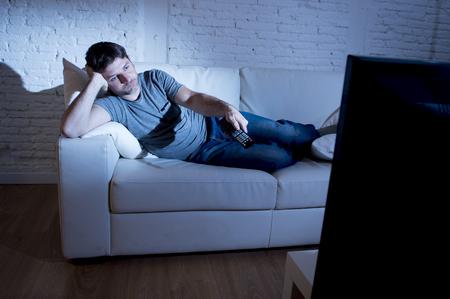 jonge aantrekkelijke man thuis liggend op de bank in de woonkamer tv kijken bedrijf afstandsbediening en het veranderen van kanaal of het volume op zoek vervelen