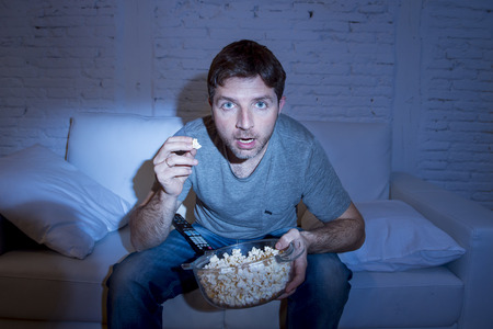mesmerized: young attractive man at home lying on couch at living room watching tv holding popcorn bowl eating and looking mesmerized and intense concentration in television addict concept