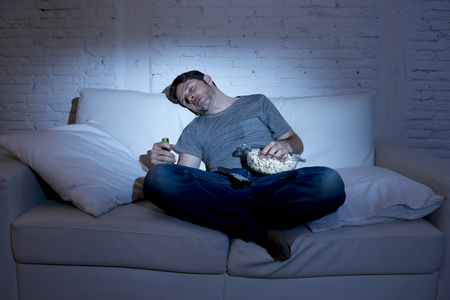 bowls of popcorn: young man at home sofa in living room sleeping while watching movie or sport in tv late at night holding popcorn bowl and beer bottle