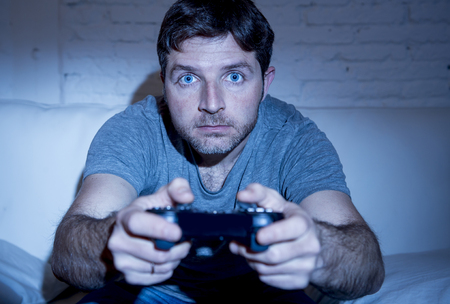 young excited man at home sitting on living room sofa playing video games using remote control joystick with freak intense face expression having fun in gaming addiction Stock Photo