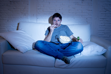 watching movie: young man sitting at home sofa in living room watching movie or sport in tv eating popcorn and drinking beer in intense and concentrated face expression in television addiction