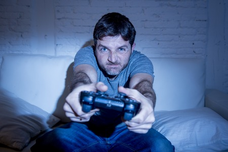 young excited man at home sitting on living room sofa playing video games using remote control joystick with freak intense face expression having fun in gaming addiction Banque d'images
