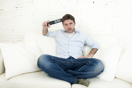 interested: young happy man watching tv sitting at home living room sofa holding remote control looking intense and very interested enjoying television program or movie