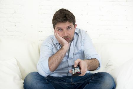 jonge man verveeld tv kijken zit thuis woonkamer sofa op zoek moe en niet plezier met het tv-programma of film met de afstandsbediening voor het veranderen van een ander kanaal Stockfoto