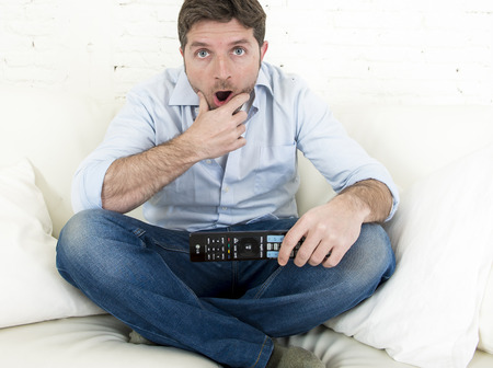 interested: young man watching tv sitting at home living room sofa holding remote control looking intense and very interested enjoying television program or movie in disbelief amazed and shock face expression