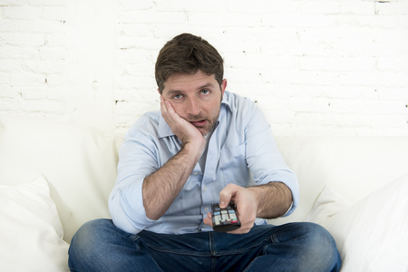 young bored man watching tv sitting at home living room sofa looking tired and not having fun with the television program or movie using remote control for changing to another channel Reklamní fotografie