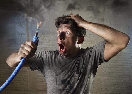 jonge man met elektrische kabel roken na huiselijk ongeval met vuile verbrand gezicht in grappige droevige uitdrukking in elektriciteit DIY reparaties gevaar concept in zwarte rook achtergrond
