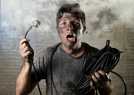 electric shock: young untrained man joining electrical cable suffering domestic accident with dirty burnt face in funny shock expression screaming crazy in electricity DIY repairs danger concept