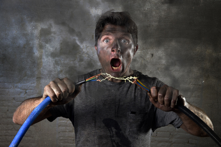 electrocute: young untrained man joining electrical cable suffering domestic accident with dirty burnt face in funny shock expression screaming crazy in electricity DIY repairs danger concept