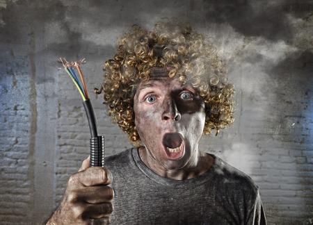 jonge man met grappige krullende pruik met elektrische kabel met roken na huiselijk ongeval met vuile verbrande gezicht en shock geëlektrocuteerd meningsuiting in elektriciteit DIY reparaties gevaar concept in zwarte rook achtergrond Stockfoto